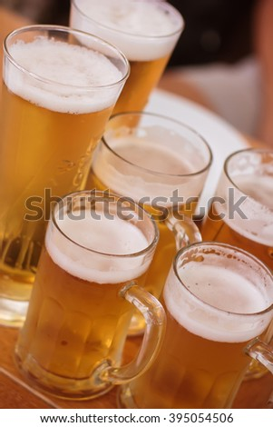 Drinking beer in a large company. Drink beer with friends. Cold light foamy beer in glass mugs on a wooden table. Beer Day. Oktoberfest. Beer tradition.