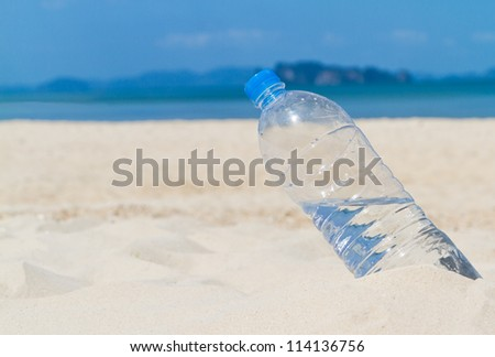 drinking bottle on the beach in sunny day - stock photo
