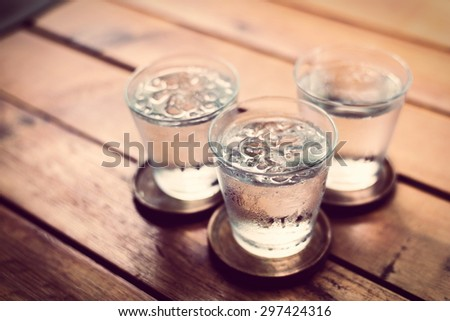 Drinking cold water into a  three glass placed on the wooden table. - stock photo