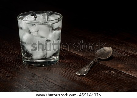 Drinking glass with ice cubes and clear liquid on the dark wooden surface. - stock photo