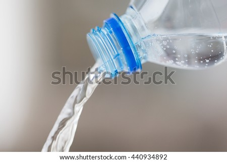 drinking, healthy eating and food storage concept - close up of water pouring from plastic bottle - stock photo