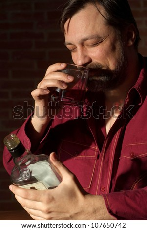 Drinking man sits quietly at his home at the table