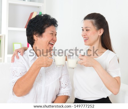 Drinking milk. Asian family drinking milk at home. Beautiful senior mother and adult daughter, healthcare concept. - stock photo