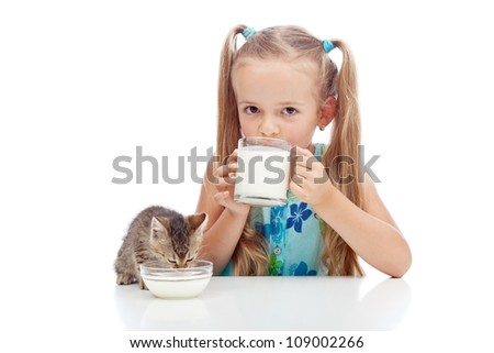 Drinking milk with my best friend - little girl and kitten enjoying dairy product - stock photo