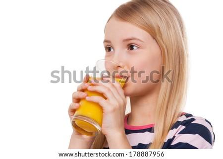 Drinking orange juice. Cheerful little girl drinking orange juice and smiling while standing isolated on white - stock photo
