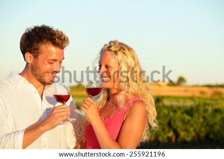 Drinking red wine couple in love. Happy people drinking rose wine alcohol laughing in summer vineyard. - stock photo