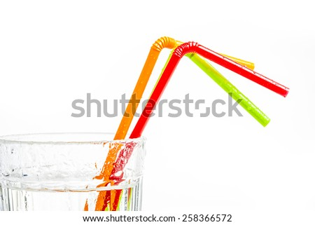 Drinking straws in the  glass of water. - stock photo