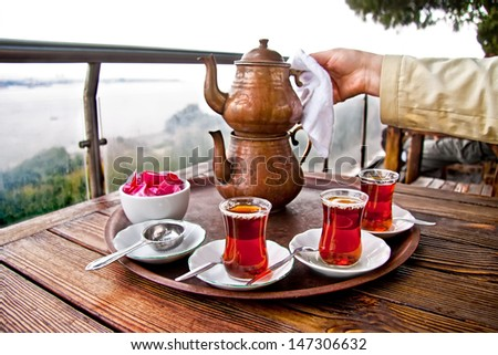Drinking Traditional Turkish Tea with Turkish tea cup and copper tea pot - stock photo