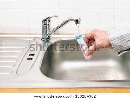 Drinking water in the test tube for chemical and microbiological analysis - stock photo