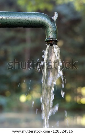Drinking water running  from an old  water pump a rural environment . - stock photo