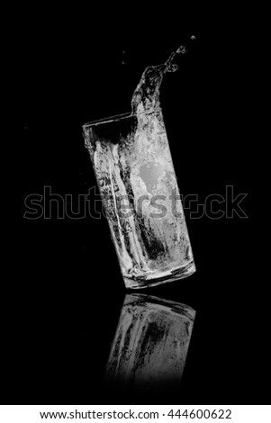 drinking water splash from glass on black background. - stock photo