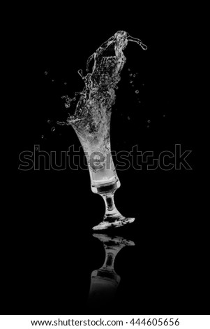 drinking water splash from glass on black background.