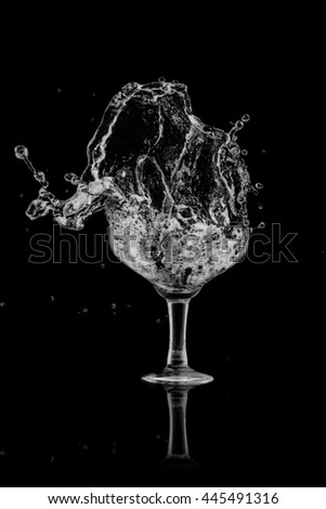 drinking water splash out of glass on black background. - stock photo