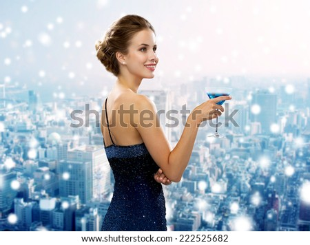 drinks, christmas, holidays and people concept - smiling woman in evening dress holding cocktail over snowy city background - stock photo