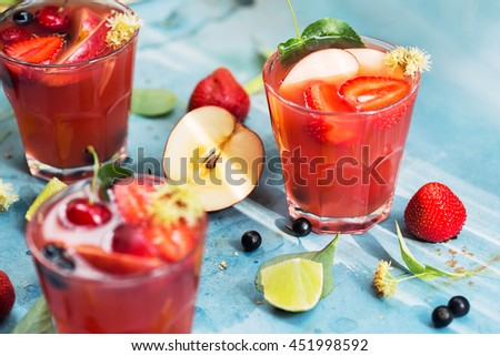 Drinks, food styling, cooking. Red cocktails with berries, strawberries, currant and apple