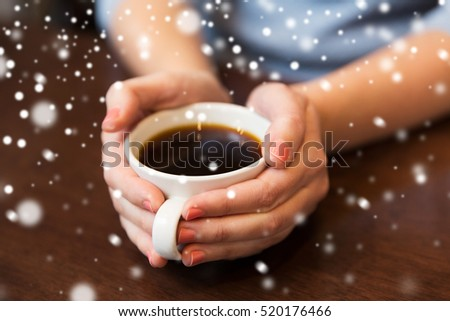 drinks, people, christmas and winter concept - close up of woman hands holding cup with hot black coffee over snow