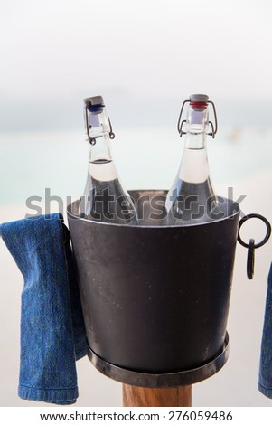 drinks, thirst, refreshment and summer resort concept - couple of water bottles in ice bucket at hotel beach - stock photo