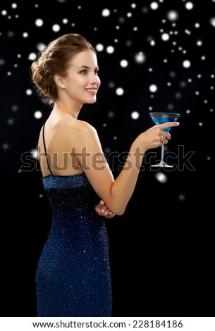 drinks, winter holidays, christmas, luxury and celebration concept - smiling woman in evening dress holding cocktail over black snowy background - stock photo