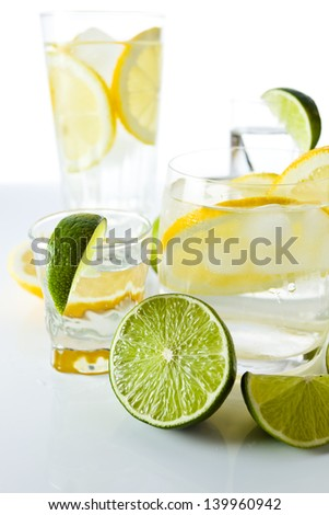 drinks with lemon and lime, shot on reflective  background - stock photo