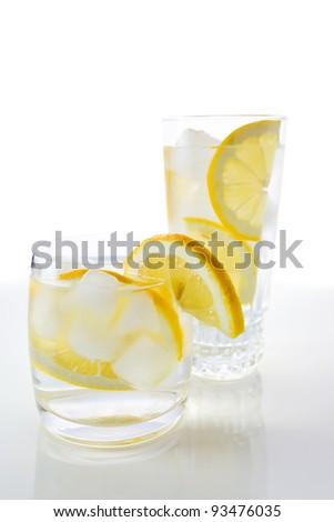 drinks with lemon, shot on reflective white background. - stock photo
