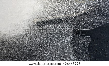 Dripping and cracked black paint on grungy metal surface - Close up 