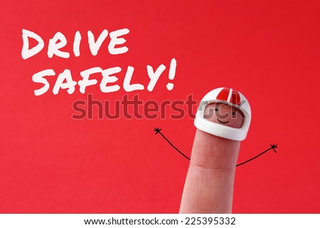 Drive safely - funny finger figure wearing a helmet with Drive safely text written on red background - stock photo