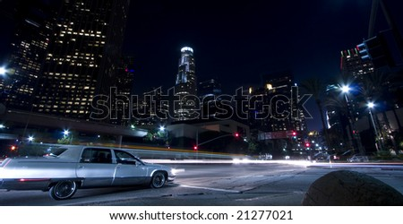 Drive through the city (one car seen with rest of traffic as trails of light) - stock photo
