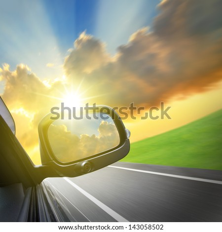 Drive to the sunshine, car and rear view mirror on the road, concept for business, speed or success - stock photo