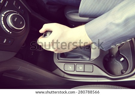 driver hand shifting the gear stick.a hand holding a car's remote control pointing to the door
