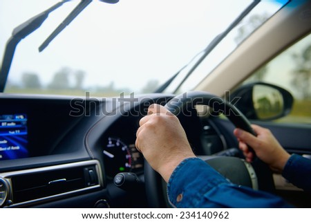 Driver hands on steering wheel into car - stock photo