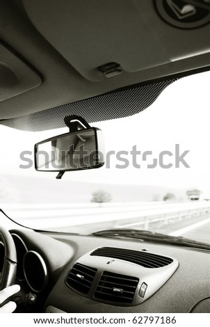 Driver in car holding steering wheel. Blurred road and sky-2 - stock photo