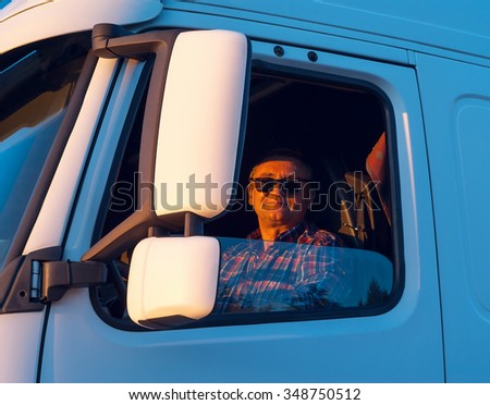 Driver in the cabin of him truck - stock photo