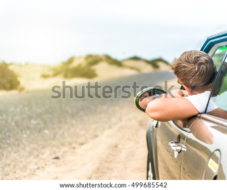 driver leaning out of car window on roadside in Lanzarote desert, Canary Island, Spain