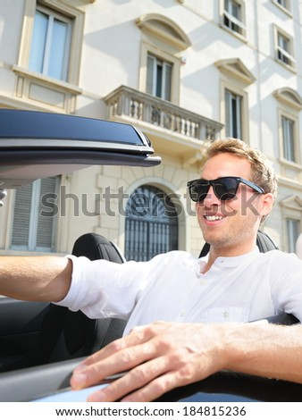 Driver - man driving car. Successful young man in convertible car wearing sunglasses in summer.