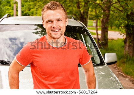 Driver of car stands about cowl and smiles against summer nature.