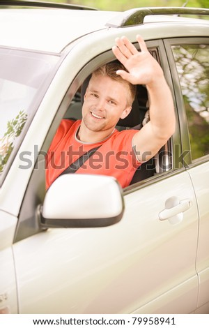 Driver of car waves hand as a sign of greeting.