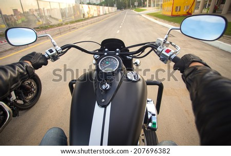 Driver riding motorcycle on an asphalt road - stock photo