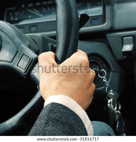 Driver's hand on steering wheel - stock photo