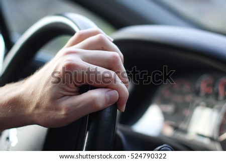 Driver's hand on the steering wheel of a car