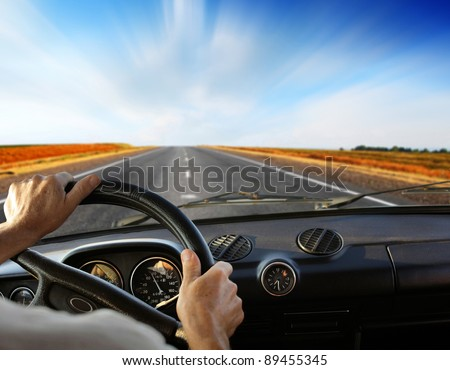 Driver's hands on a steering wheel - stock photo