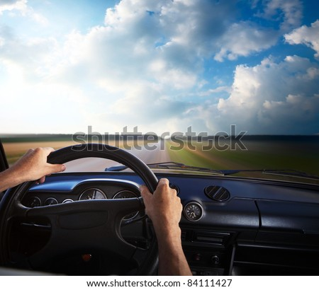 Driver's hands on a steering wheel and motion blurred road