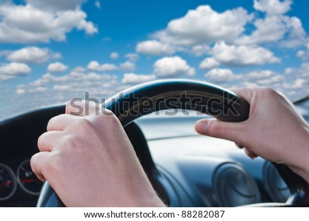Driver's hands on a steering wheel of a car - stock photo