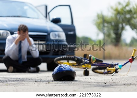 Driver sitting on the street  after car accident - stock photo