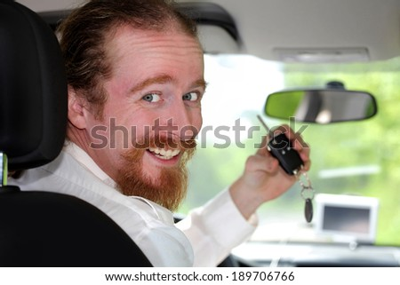 driver smiling sitting in car and showing new car keys  - stock photo