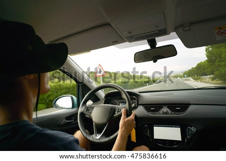 Driver travels in his car on motorway, view from inside the car. Hands on steering wheel, cold summer weather