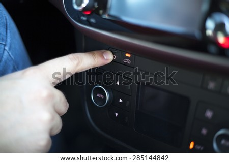 Driver turning on air conditioner on the dashboard of a car
