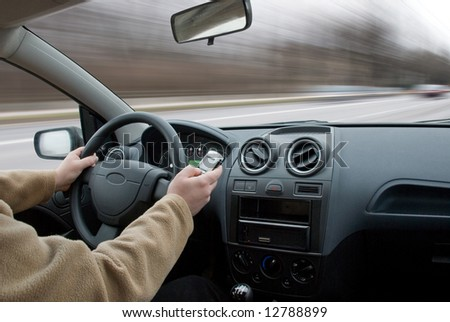Driver using cell phone in car blurred motion - stock photo