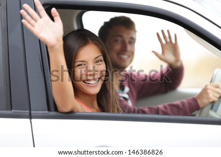 Drivers driving in car waving happy at camera. Young couple on road trip in new car. Interracial happy couple. - stock photo