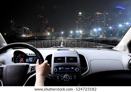 Drivers hands on the steering wheel inside of a car