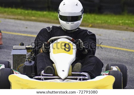 Drivers racing high speed around a track in a go-kart - stock photo